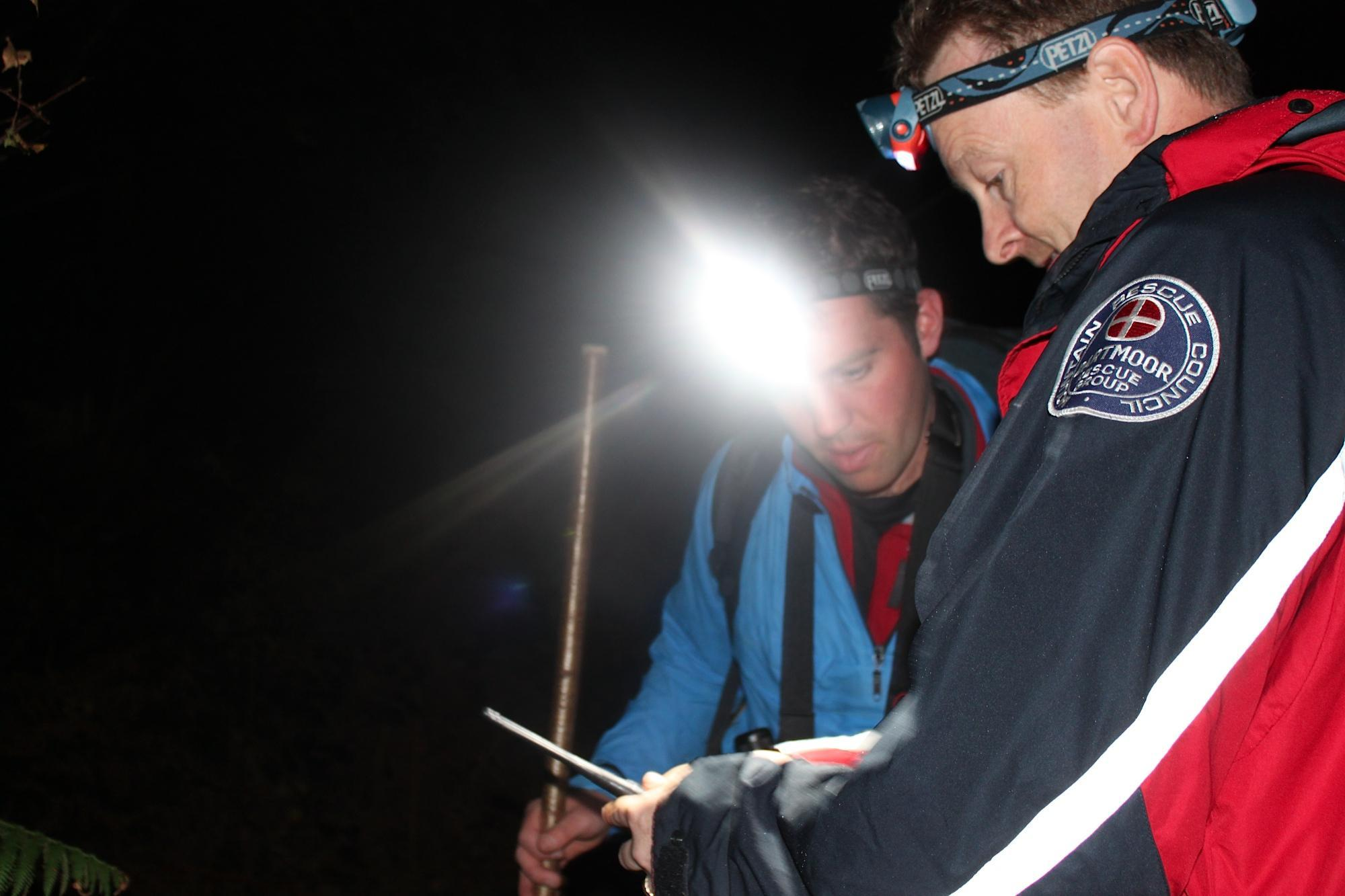 Dartmoor Search and Rescue Team - Ashburton members consulting a map during a night search