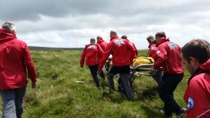 Dartmoor Rescue transporting a casualty on a stretcher to the ambulance